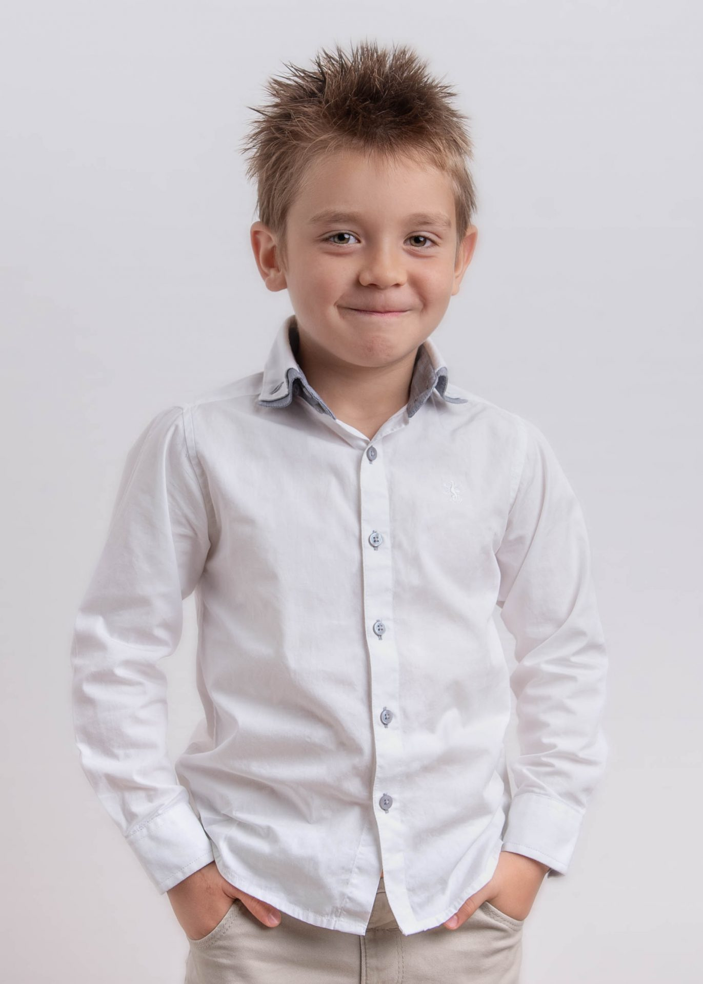 studio portrait of boy with spiky hair and white shirt against white background