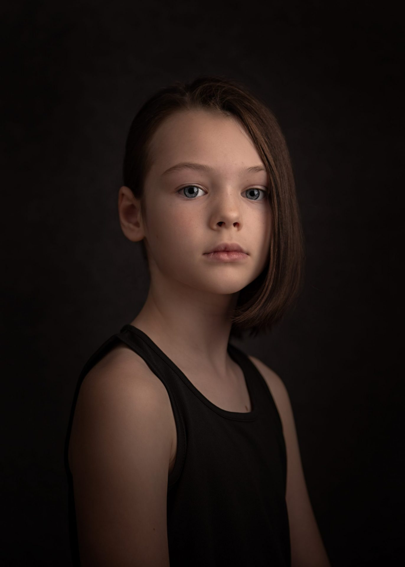 studio portrait of a girl in a black vest and undercut hair staring seriously at the camera
