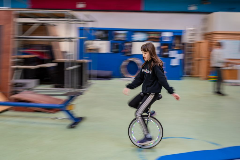 panning shot of girl riding a unicycle