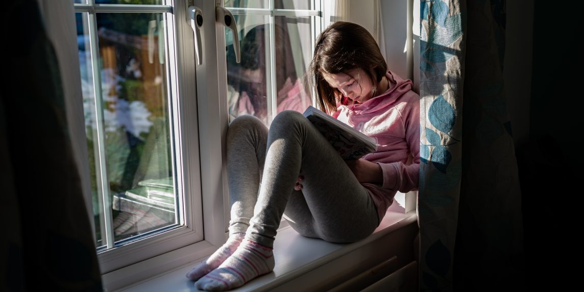 girl sitting on window sill reading and learning at home
