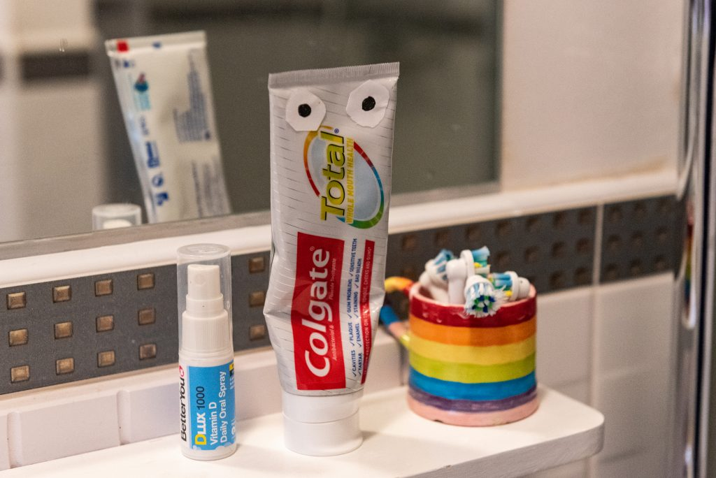 toothpaste tube with stuck on eyes on shelf in bathroom