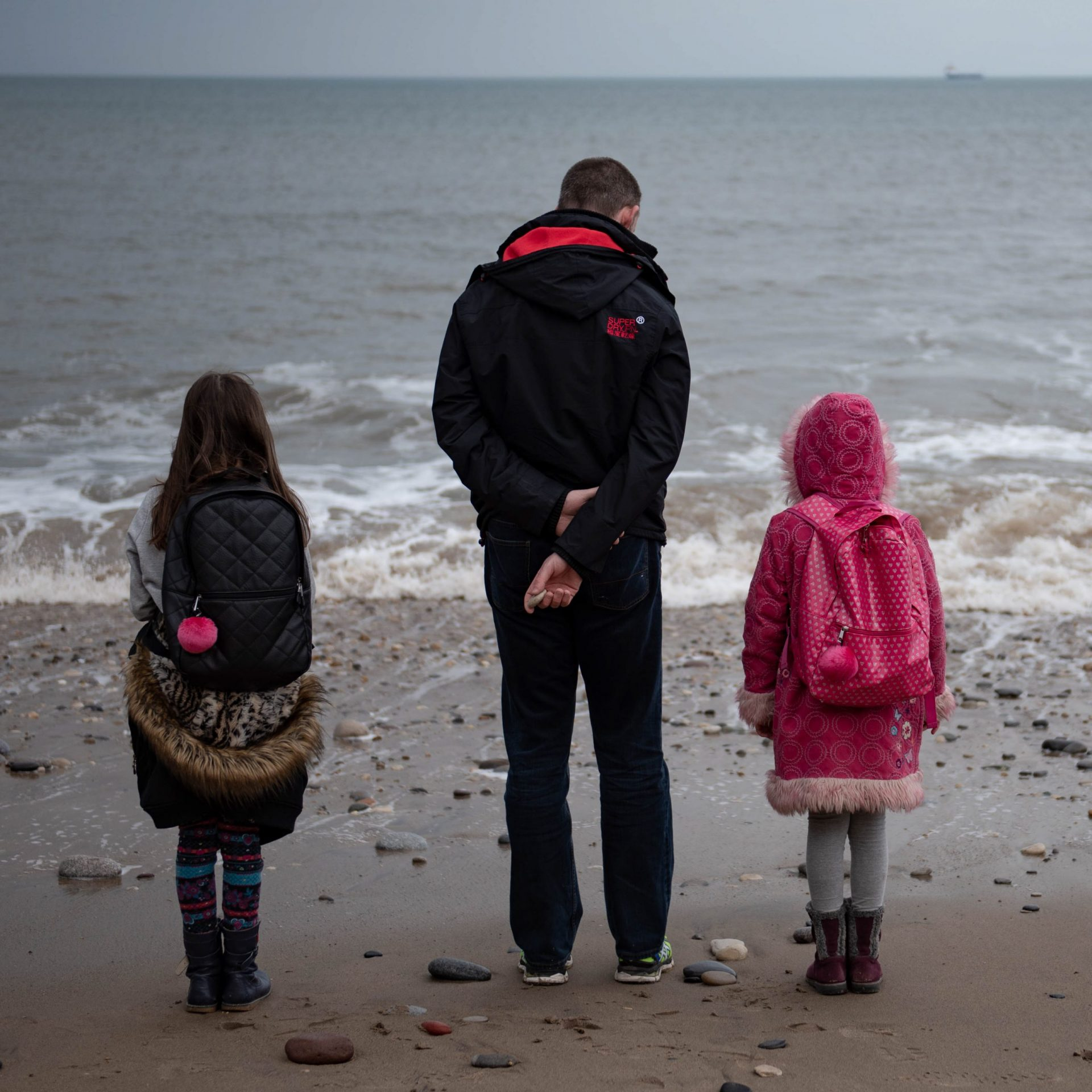 father and two child standing at the edge of the sea in winter