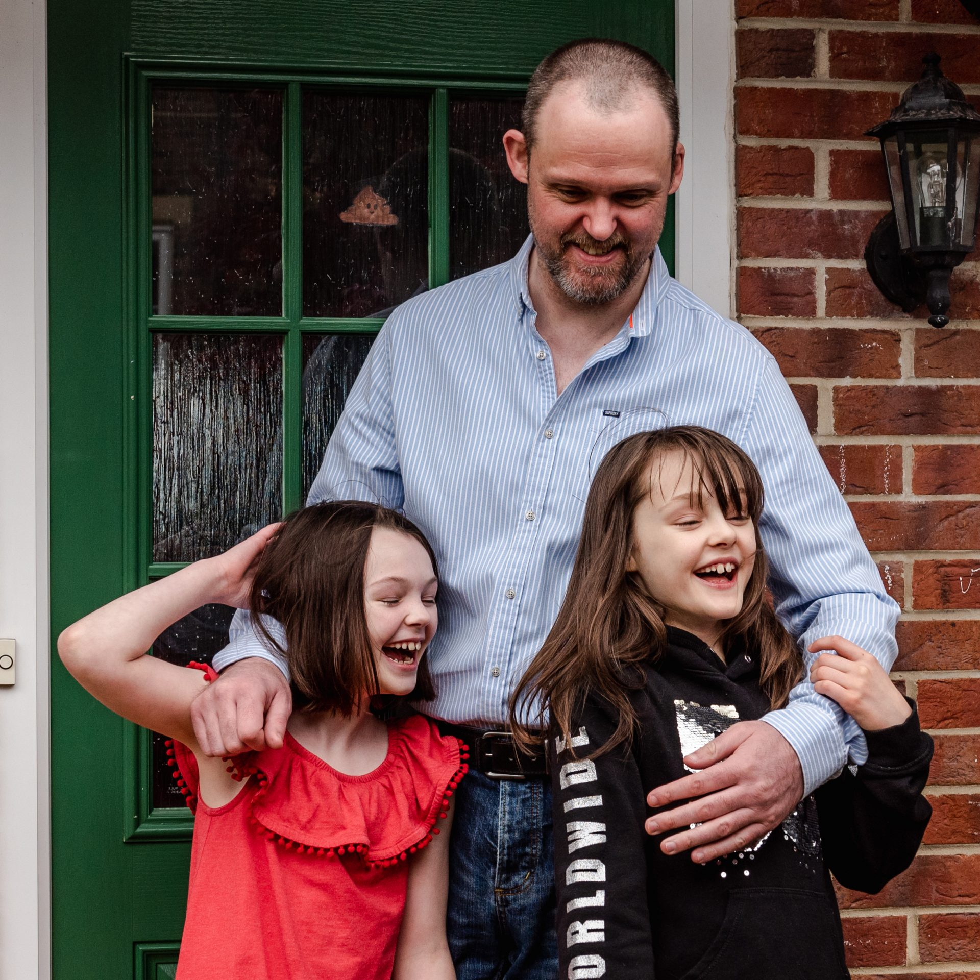 father and two daughters laughing on doorstep