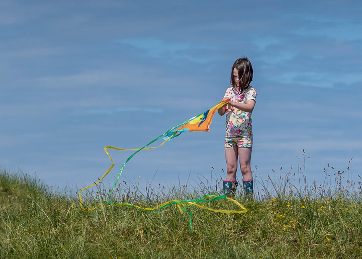 girl untangling a kite stood against a clear blue sky