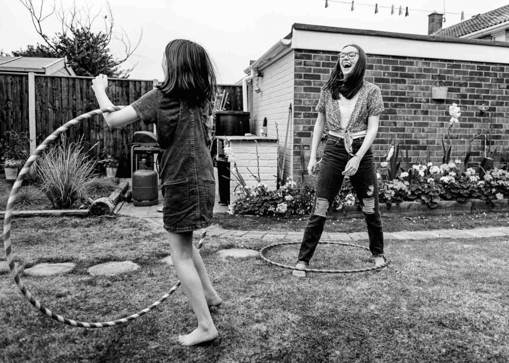 girls in garden hula hooping and laughing