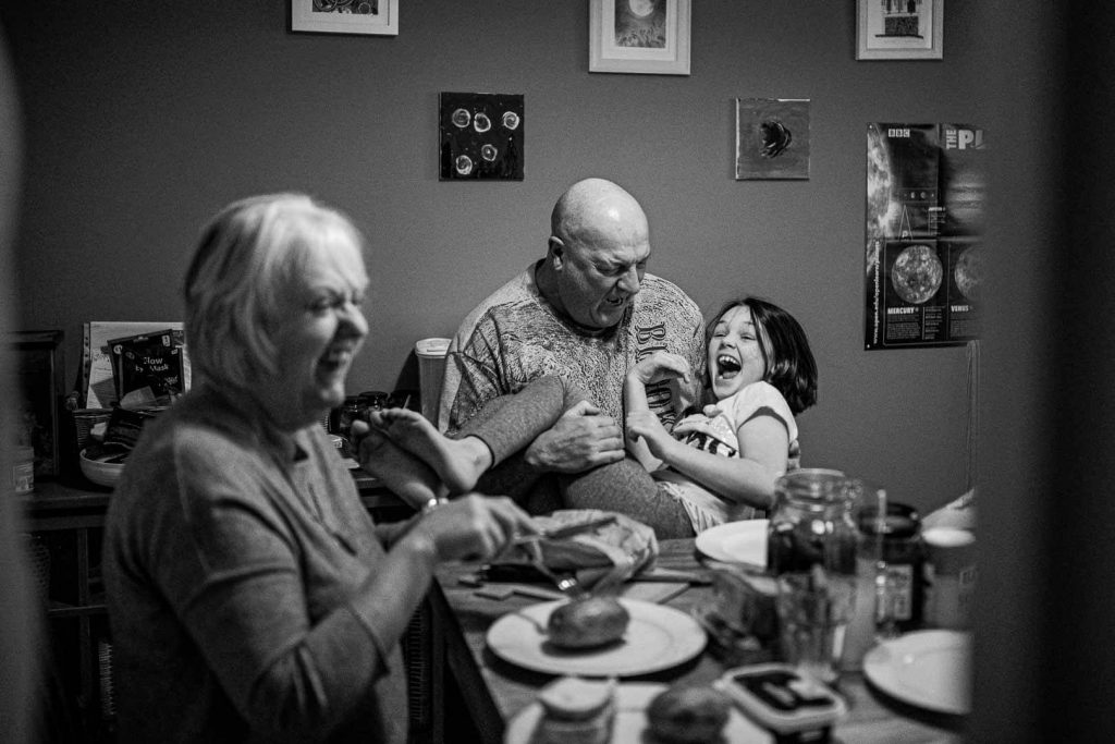 child and grandparents around dinner table laughing